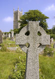 Church and cross. Old celtic cross with church and steeple in background Stock Images