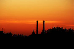 Church cupolas and factory chimneys on red sky at sunset Royalty Free Stock Photography