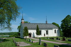 The church in Dalby, Uppland, Sweden. The church in Dalby with the oldest parts from 13th century is placed on a cape close to the waterway to Uppsala, in stock photography