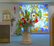 Church Decorated for a Wedding. Interior of a church decorated for a wedding with fowers and stained glass Royalty Free Stock Photography