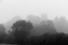 Church in deep fog on hill side in B&W Stock Image