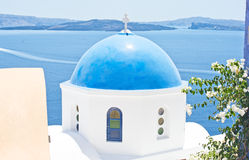 Church dome with Caldera background. Stock Photos