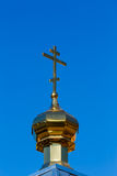 Church dome with a cross against,  blue sky Stock Photo