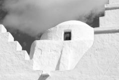 Church dome with small window in Mykonos, Greece. Chapel building architecture detail. White church on cloudy blue sky. Religion and cult concept. Summer royalty free stock photography