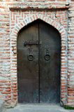 Church door. Geogian old church metal door and red brick wall Royalty Free Stock Photography