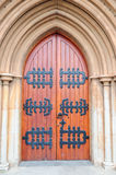 Church door. Antique church door with black steel decoration in arch on an outside stone wall of a historical church building Royalty Free Stock Photo
