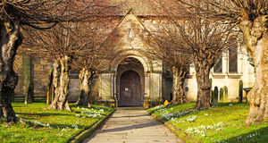 A Church Door, viewed down the church path. The view of a church door looking down the churchyard path lined with snowdrops in the evening sunshine royalty free stock images