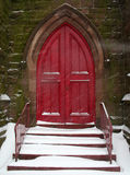 Church Doors. Red church doors in snowstorm royalty free stock image