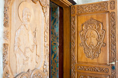 Church doors. With saints and symbols carved in hard wood stock images