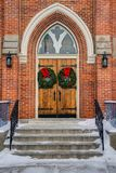 Church doors with wreaths. Gothic oak wooden church doors with ornate metal hardware, wreaths hung for Christmas, and red bow stock image