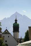 Church down to the mountain, Innsbruck. Idea of a postal card of Innsbruck, with a church roof and the mountains in background royalty free stock images