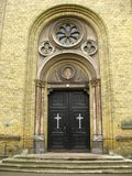 Church entrance. Yellow brick church entrance - wooden doors with the crosses Royalty Free Stock Photo