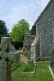 Church entrance and headstones. Headstones and side view of church entrance at St Peters Church in Upper Beeding, West Sussex, UK. Upper Beeding is a village on stock image