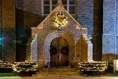 Church Entrance at Night. Entrance to a large church at night, decorated with Christmas lights and wreaths for the holidays Royalty Free Stock Photo