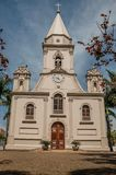 Church facade and belfry in front of a small cobblestone square with evergreen garden, in a sunny day at São Manuel. A cute little town in the countryside stock photography