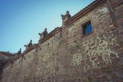 Church facade with gargoyles in red, Villafamés rural villa in Stock Photos