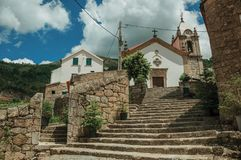 Church facade and steeple on top of stone staircase. Old countryside church facade and steeple on top of stone staircase, in a sunny day at Alvoco da Serra. A royalty free stock image