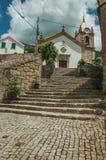 Church facade and steeple on top of stone staircase. Old countryside church facade and steeple on top of stone staircase, in a sunny day at Alvoco da Serra. A stock photography