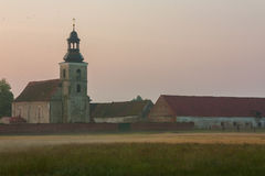 Church and farm buildings. Small rural church  and building brick farmhouse  in the morning mist.. Photo taken in June by sunrise. Idyllic rural landscape in the Stock Photos