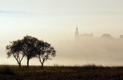 Church in the fog. With a tree in the foreground Royalty Free Stock Images