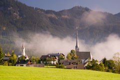 Church in fog in dramatic morning light. In an typical austrian village, with forrest hills in background Stock Images