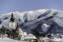 Church in the foreground and temple high mountains full of snow Stock Photo