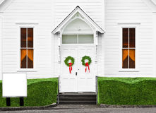 Church Front Christmas Wreaths. The double door entrance to this church has Christmas Wreaths. The blank sign is ready for your message stock image