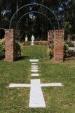 Church garden with cross and Virgin Mary. Church garden with stonework cross, archway and statue of Virgin Mary Royalty Free Stock Photos