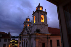 Church with glowing bell tower at night. The Church Paroquial de Sao Paulo in the Cais Sodre area of Lisbon with its bell tower bells lit up by lights inside Stock Photos