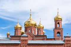 Church of the Golden domes. Beautiful church of the Golden domes against the sky with clouds. The walls and towers are made of red brick. Can symbolize both royalty free stock photography