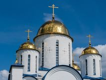 Church with golden domes and crosses on blue sky background.  stock image
