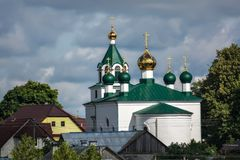 Church with golden domes. The Orthodox Church with golden domes and a green roof, towering above the roofs of houses, against the blue sky royalty free stock photos