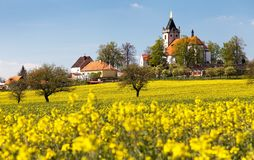 Church and golden rapeseed field Stock Photo