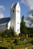 Church and graveyard. Scenic view of white church with landscaped gardens and graveyard in foreground Royalty Free Stock Photo