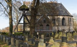 Church and Graveyard in Wanneperveen. Wanneperveen, The Netherlands - November 24, 2016: Church in Wanneperveen with the graveyard and the `Klokkenstoel royalty free stock photos