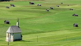 Church in a green grass field with cottages royalty free stock photography
