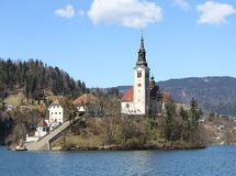 Church with a high Bell Tower on the island on Lake Bled in Slov Stock Photo