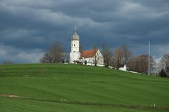Church on hill. Bavarian church on green hill with dark sky on background Royalty Free Stock Image
