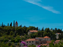 Church on hill. Church on top of the forest hill, with houses and clear blue sky in Sutivan on island Brac in Croatia Stock Images