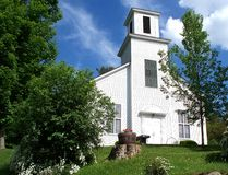 Church on the Hill. A white clapboarded church sits on hill on a warm spring day in Vermont Stock Photos