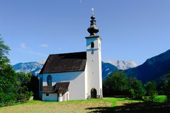 A church on a hill in front of the Alps stock image