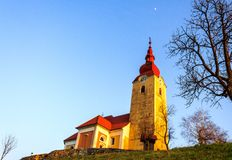 Church on the hill and the moon. The church on the hill in the village with the evening sunlight at countryside of Slovenia and the moon on sky Royalty Free Stock Photography