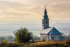 Church on a hill at sunset. Church on a hill over the hazy rural valley at sunset. lovely autumn countryside scenery Stock Photos