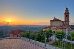 Church and hills of Langhe at sunset. Stock Photos