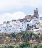 Church on a hillside. Blue sky and white clouds on the Church of Arcos de la Frontera in a hillside, surrounded by white houses Stock Photography