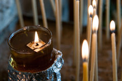 Church holy candle burning in oil Royalty Free Stock Photos