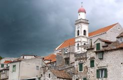 Church of the Holy Cross. Distinctive tower of church of the Holy Cross in old Croatian town Šibenik, dark, ominous clouds advancing Royalty Free Stock Image
