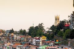 Church on the horizon with other buildings in shimla india. Shimla, India - 27th Apr 2018: Church on the horizon behind some trees and lots of buildings in the Royalty Free Stock Photography