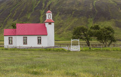 Church on Iceland. Church with red roof on Iceland with some small trees and mountains in the background Stock Photos