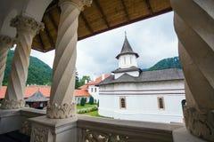 Church inside Sambata de Sus Monastery seen trough a colonade in Stock Photo